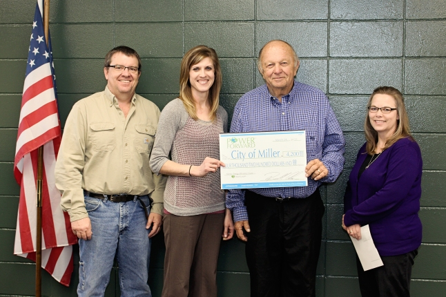 Heartland Communications Manager Ann Hyland, second from left, presents an energy efficiency grant to Miller Electric Superintendent Bill Lewellen, Mayor Ron Blachford and Finance Officer Sheila Coss.