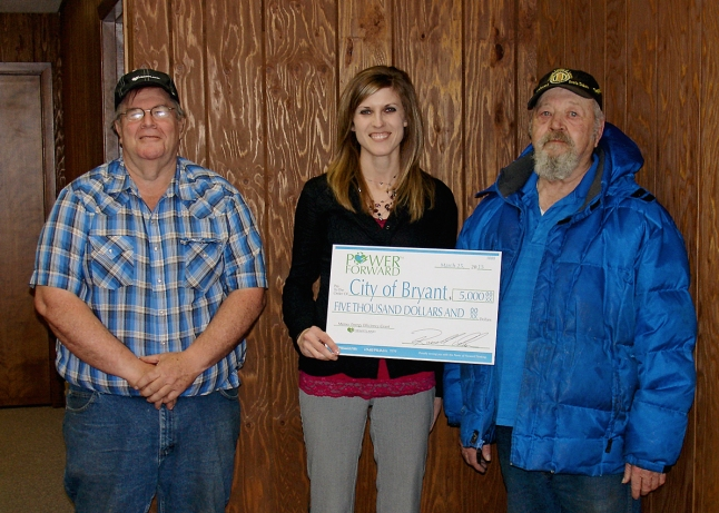 Heartland Communications Manager Ann Hyland, center, presents an energy efficiency grant to Bryant Electric Superintendent Garry Ladwig and Mayor Albert Yalowizer.